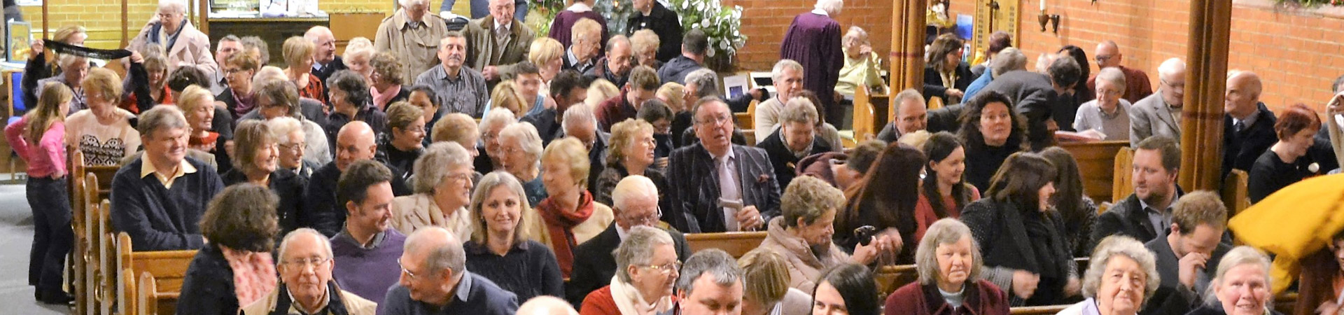 Rows of pews filled with people talking before an advent service