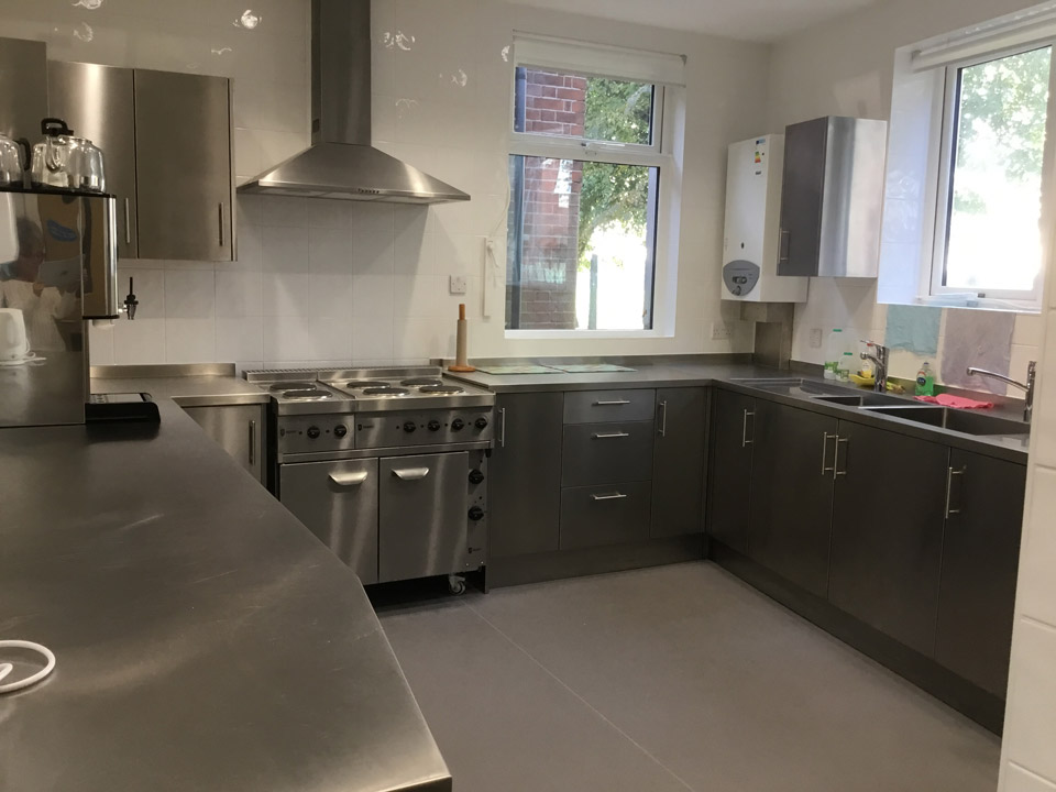 Modern, spacious kitchen with stainless steel worktops, industrial oven, sinks, boiler and windows.