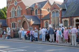 People queuing and chatting outside the church on a bright sunny day