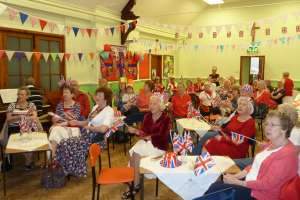 Ladies singing and waving union jack flags at a lunch party to celebrate the Queens birthday. Colourful bunting hanging from the ceiling