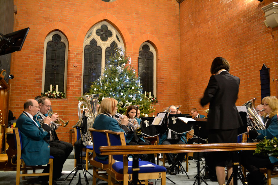 Brass band playing during a Christmas service. Conductor in front, a Christmas in the background