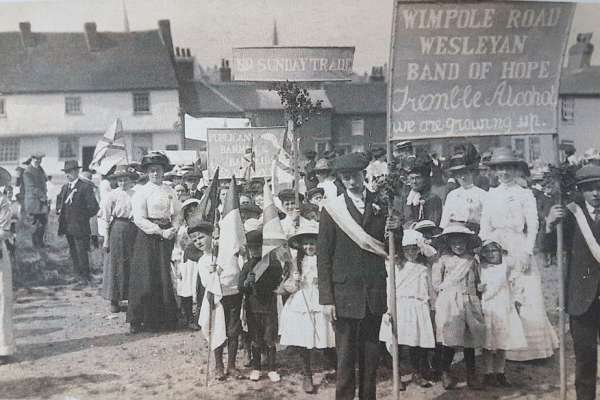 Black and white photo of a church procession. Adults and children, smartly dressed, carrying banners