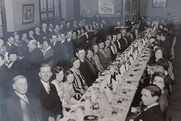 Black and white photo of a formal church lunch. Two long lines of tables with men, women and children seated on either side.
