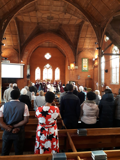 Congregation singing hymns during a Sunday service. Choir in the background, with the wooden ceiling of the church visible.